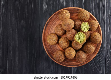 close-up of delicious Falafel balls on clay plate on black wooden table, healthy life concept, horizontal view from above