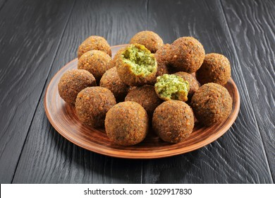 close-up of delicious Falafel balls and one is broken to pieces on a clay plate on black wooden table, healthy life concept, horizontal view from above