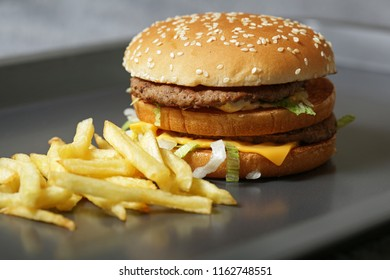 Close-up of delicious fresh burger with lettuce, cheese and onion and fries on a dark background