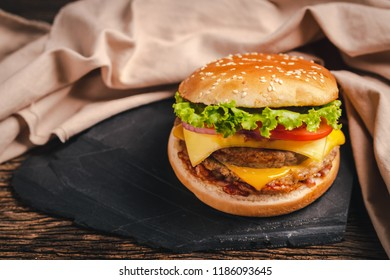 Close-up of delicious fresh home made burger with lettuce, cheese, onion and tomato on black stone and wood background