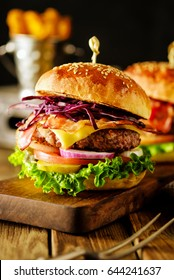 Closeup of delicious fresh homemade hamburger on wooden  dark background.