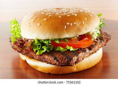 closeup of a delicious hamburger with salad and tomato on wood grain