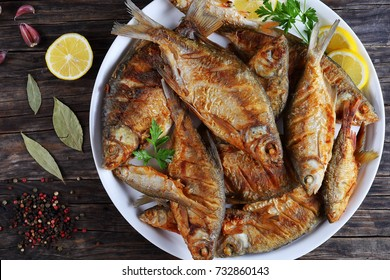 close-up of delicious hot fried mix of freshwater fish marinated with lemon slices, bay leaf, spices on white platter on old dark rustic table, horizontal view from above