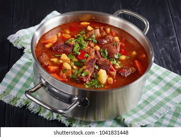 close-up of delicious hot hungarian goulash with beef meat, paprika, vegetables andcsipetke - small egg noodles in stainless steel casserole on black wooden table, classic recipe, view from above