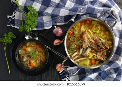 close-up of delicious Icelandic Lamb Soup with vegetables and spices or kjotsupa in a stainless steel casserole pan  and in bowl on wooden table with kitchen towel, traditional recipe, view from above