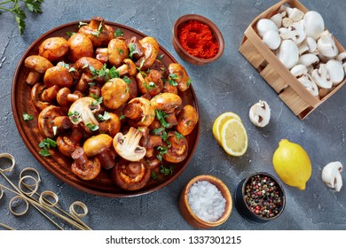 close-up of delicious lightly fried champignons, Champinones Al Ajillo, Spanish Garlic paprika Mushrooms on an earthenware plate with ingredients on a concrete table, view from above