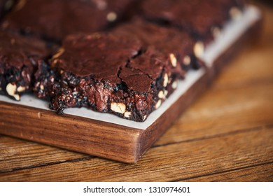 Closeup of delicious looking freshly made gooey chocolate brownies with nuts sitting on a wooden serving board on a bakery table