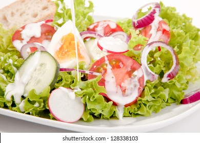 Closeup of a delicious mixed green salad with egg, onion, tomato and cucumber drizzled with a tangy salad dressing for a healthy meal