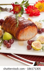 Closeup of delicious one piece roasted bacon - wrapped pork loin with roasted garlic, grapes, figs, and fresh rosemary.