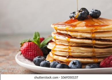 Close-up delicious pancakes, with fresh blueberries, strawberries and maple syrup on a light background. With copy space. Sweet maple syrup flows from a stack of pancake