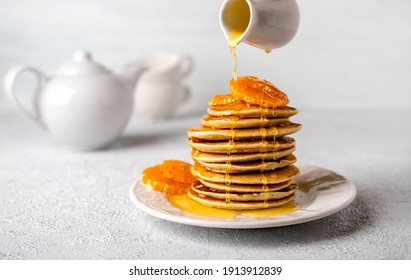 Close-up delicious pancakes with honey or maple syrup for breakfast on a light background. The syrup is poured onto the pancakes.