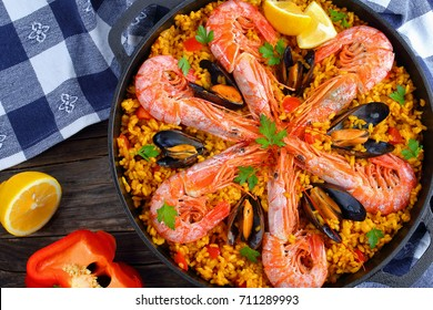 close-up of delicious seafood valencia paella with king prawns, mussels on savory creamy saffron rice with spices and lemon wedges in pan, on wooden table, view from above