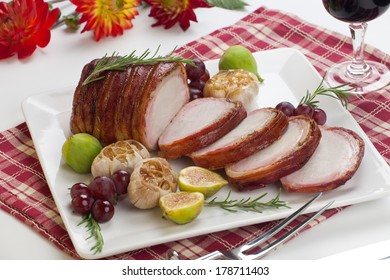 Closeup of delicious sliced roasted bacon - wrapped pork loin with roasted garlic, grapes, figs, and fresh rosemary.