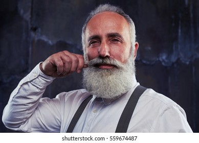 Close-up of delighted senior man twirling moustache and smoothing his grey beard. Man taking care of his bushy beard and mustache