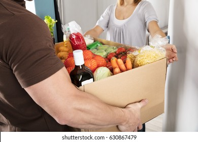 Close-up Of A Delivery Man Giving Grocery Cardboard Box To Woman