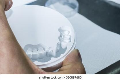 Closeup  of dental technician is extracting teeth in the zirconia disc.
