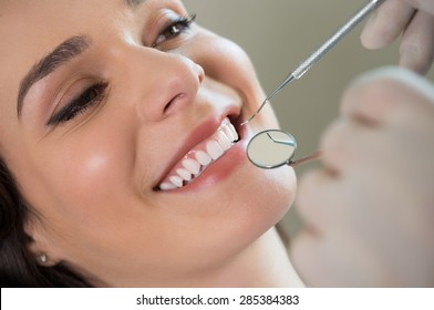 Closeup of dentist examining young woman's teeth