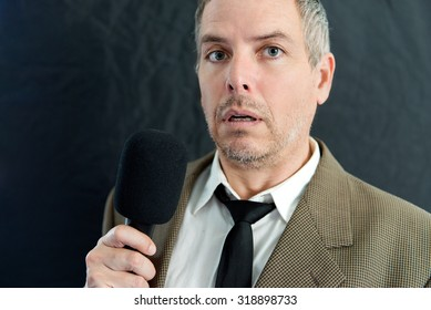 Close-up of a depressed man speaking into microphone.