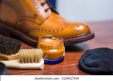 Closeup of Derby tan Male Boots With Cleaning Accessories and Wax In Front.Horizontal image Orientation