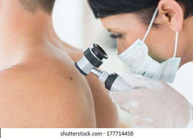 Closeup of dermatologist examining mole on back of male patient in clinic