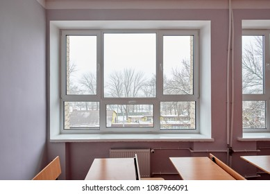 Closeup of desk and chairs in light classroom with big window
