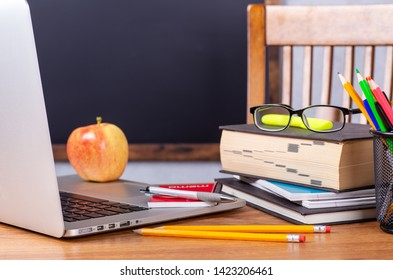 Closeup of a desk with various school items and a blank blackboard in background for copy space