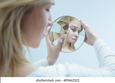 Close-up of a desolated young woman looking into a broken mirror which she is holding in her hands