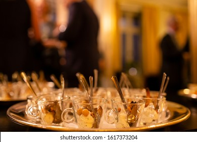 Close-up of dessert tray at a prestigious mingle event, with blurry dressed up people in the background.