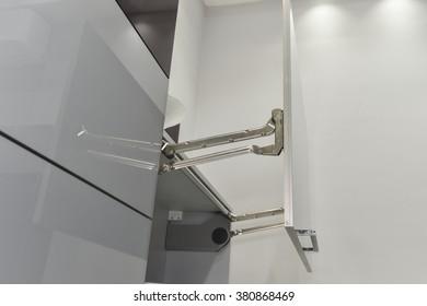 Closeup detail of an actuator hinge on door of a kitchen cupboard