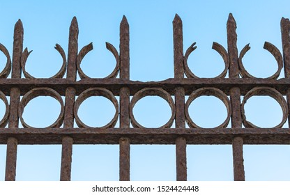 closeup detail of an antique rusting wrought iron fence at the old train station in Tel Aviv Israel with a clear blue sky background