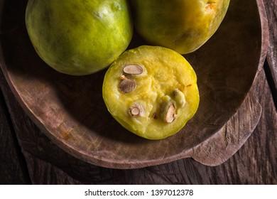 closeup detail of araza fruit in rustic wooden bowl