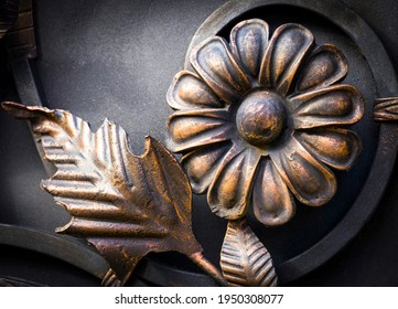 Close-up detail of beautiful vintage forged metal big yellow and red flower decorating iron gray fence,