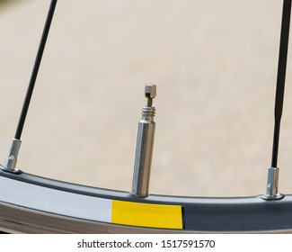 """Closeup detail of bicycle tire valve stem in the """"open"""" position on a road bike wheel"""