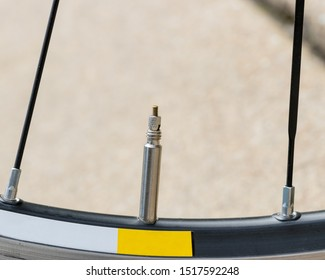 """Closeup detail of bicycle tire valve stem in the """"closed"""" position on a road bike wheel."""