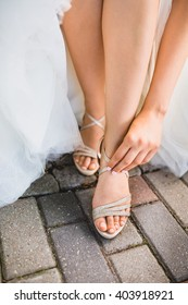 Closeup detail of bride putting on high heeled sandal wedding shoes