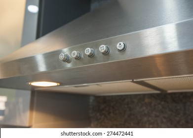 Closeup detail of buttons on metal cooker hood extractor fan with spotlight in luxury kitchen