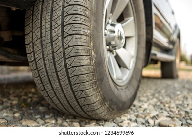 Close-up detail of car wheel with aluminum disc and black rubber tire protector on light blurred outdoors background. Transportation, safety, reliability, modern design concept.