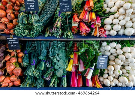 A closeup detail of a colorful display of organic vegetables at an outdoor farmers market in Seattle.