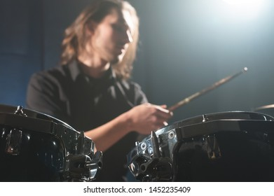 Close-up detail of a drum set against a blurred out-of-focus drummer with drum sticks