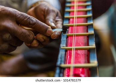 Closeup / detail of elderly Indian man's hands building a Sitar string instrument, carving the wooden neck piece, Bangalore, South India
