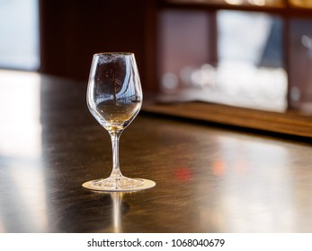 Close-up detail of an empty wine glass with smudged rims and multiple reflections on a coaster and wooden bar counter. Shallow depth of field. Kyoto, Japan. Travel and party concept.