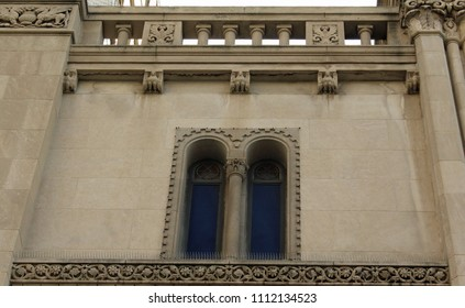 Close-up detail of a granite and stone building in Italian and French Romanesque style, including carved flowers, arched windows, arched dentil molding, corbels carved as birds, and short columns.