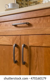 Close-up detail of high quality cherry wood cabinets with bronze cabinet hardware in contemporary upscale home kitchen interior