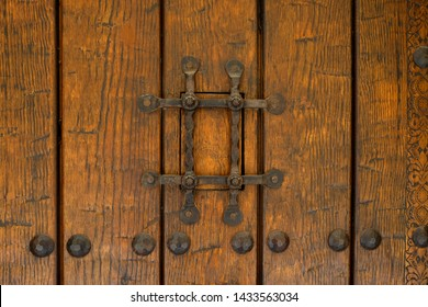 Close-up detail of an iron metal grate covering a peep window or peephole in an old door in Granada, Spain.