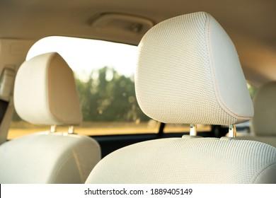 Closeup detail of light beige car headrests.