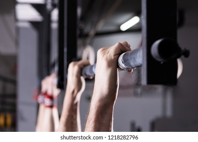 Closeup detail of male hands holding a pull-ups bar in a gym