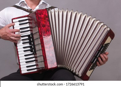 Closeup detail of a man in a white shirt playing the red accordion. Hands close-up