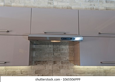 Closeup detail of metal cooker hood extractor fan with spotlight in luxury kitchen and cupboards