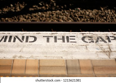 close-up detail of a 'mind the gap' warning painted onto a train railway platform on a white background and bricks in rural New South Wales, Australia