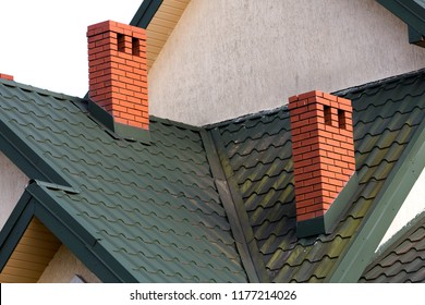 Close-up detail of new modern house top with shingled green roof, high brick-red chimneys and stucco walls. Professionally done building and construction work, real estate property, contract concept.
